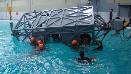 Alunos utilizando equipamento que simula a queda de aeronave em ambiente aquático