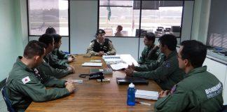 Ten Cel Ledwan Salgado Cotta, cmt do Btl RpAer, ao centro realizando um briefing com os 7 militares do CBMMG que irão participar do programa de treinamento.