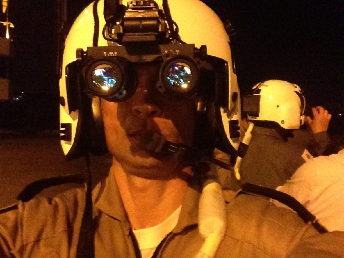 Ten Cel Ledwan Salgado Cotta realizando os ajustes dos óculos de visão noturna antes do voo