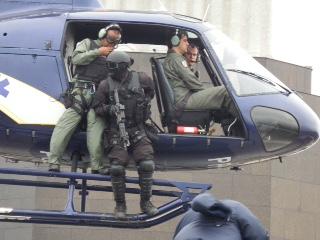 """Integrante da Unidade de Intervenção Tática do BOPE prepara-se para descer da aeronave Esquilo (PP-ECF, """"Fênix 08"""") do GAM pairando sobre uma área extremamente exígua na base da estátua do Cristo Redentor. (Imagem: Ronaldo Olive)"""