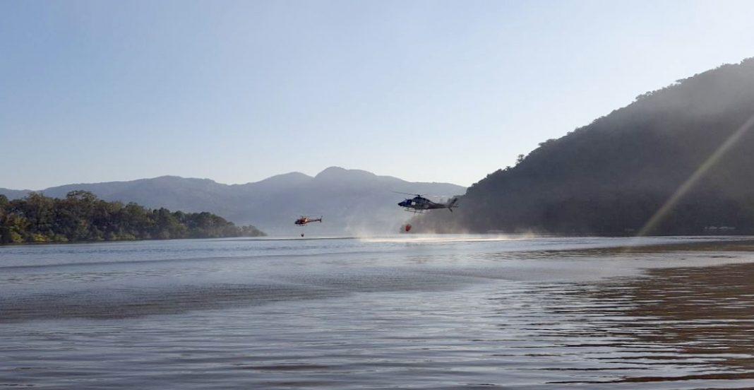 Os helicópteros Arcanjo 01 dos Bombeiros e Águia 02 da PM trabalharam lado a lado no combate às chamas - PM/Divulgação.
