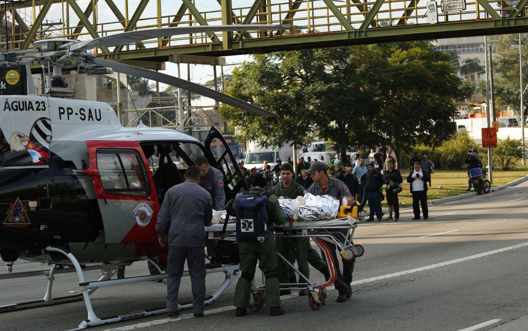 Policial militar é levado para dentro do helicóptero Águia, da PM (Foto: Renato S. Cerqueira/Futura Press/ Estadão Conteúdo)