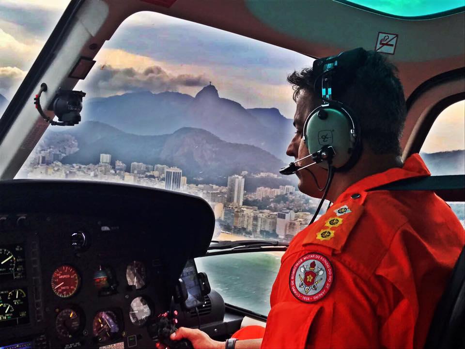 Oficial do Corpo de Bombeiros Militar do Rio de Janeiro pilotando helicóptero nas operações aéreas do Estado, salvando vidas.