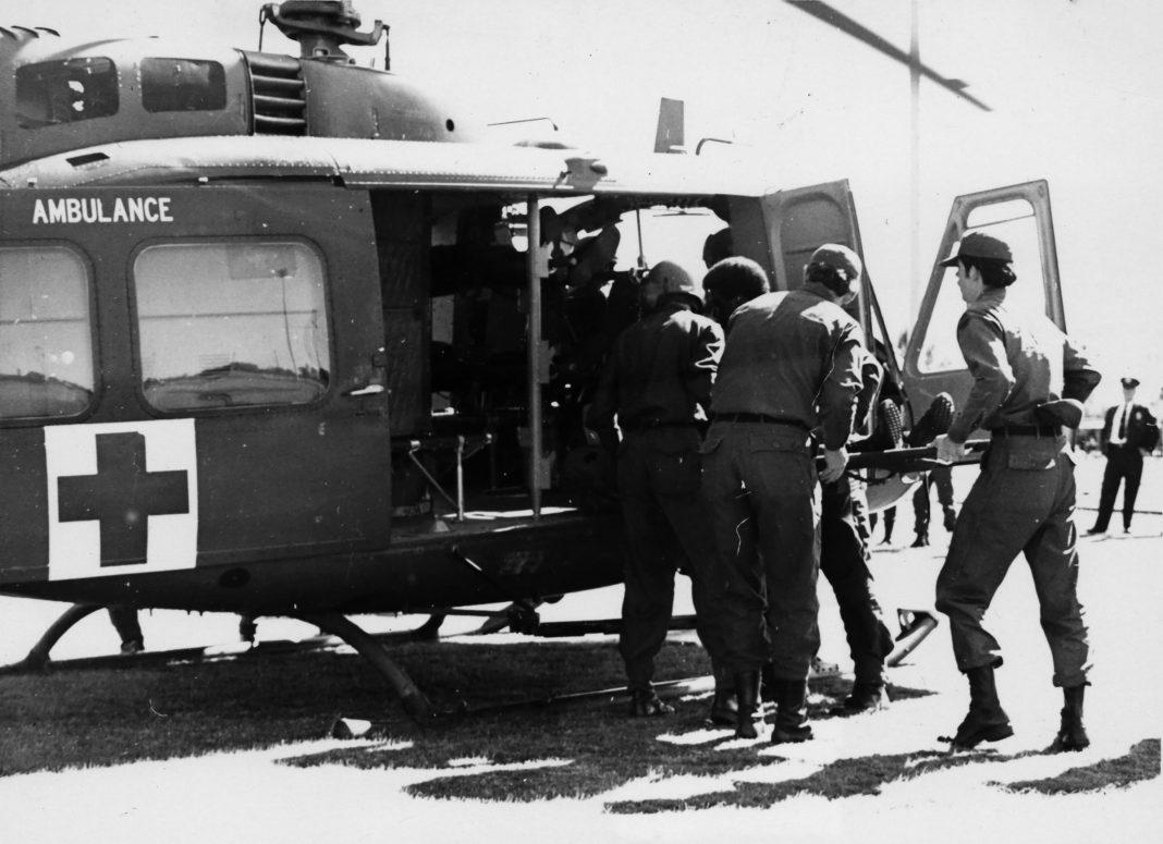 Uma equipe de MAST baseada em San Antonio carrega um paciente em um helicóptero de medevac em torno de 1970. O programa MAST foi projetado para trazer técnicas médicas de emergência do campo de batalha para civis nos EUA. MUSEU DO DEPARTAMENTO DE MEDICINA DO EXÉRCITO