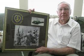 Jim Eberwine, um ex-piloto da Dustoff, mostra uma série de fotos que ele juntou para comemorar o trabalho de aviadores feridos ao serviço do Comando Médico do Exército dos EUA. CRÉDITO CARSON FRAME / AMERICAN HOMEFRONT