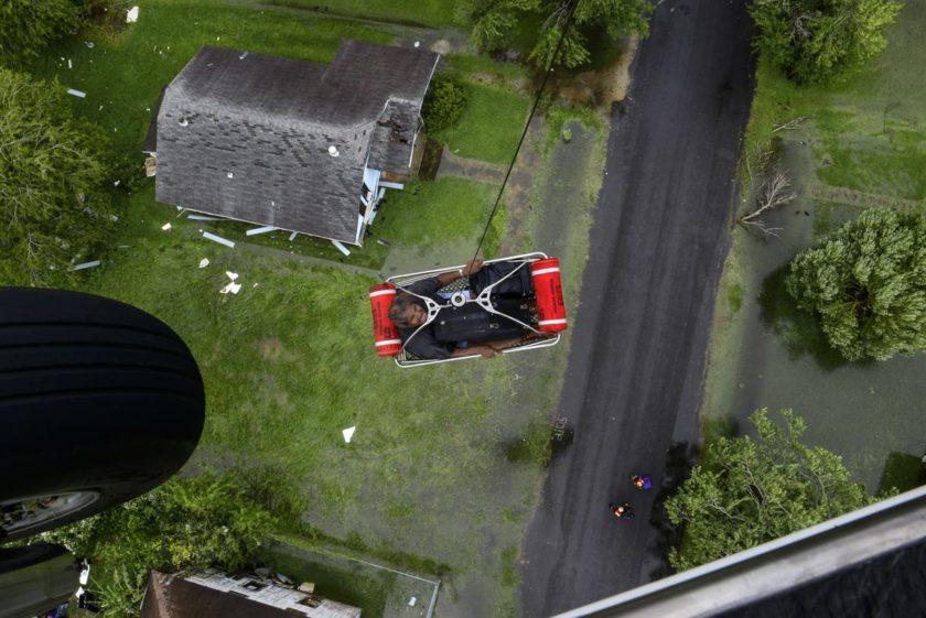 Os guardas da costa levam um residente em um helicóptero enquanto respondem aos pedidos de busca e salvamento após o furacão Harvey em torno de Beaumont, Texas, 30 de agosto de 2017. Foto via DoD.