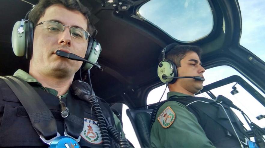 Capitão William de Freitas Schorcht, a esquerda, a bordo do helicóptero Fênix do GAM da PMERJ.