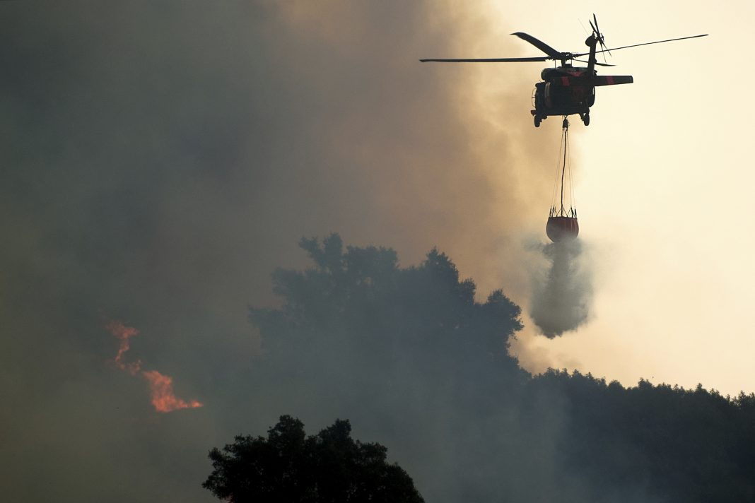 "A helicopter drops water while battling the Thomas fire in Ojai, Calif., on Thursday, Dec. 7, 2017. The biggest and most destructive of the windblown fires raking Southern California shut down one of the region's busiest freeways Thursday and threatened Ojai, a scenic mountain town dubbed ""Shangri-La"" and known for its boutique hotels and New Age spiritual retreats. (AP Photo/Noah Berger)"