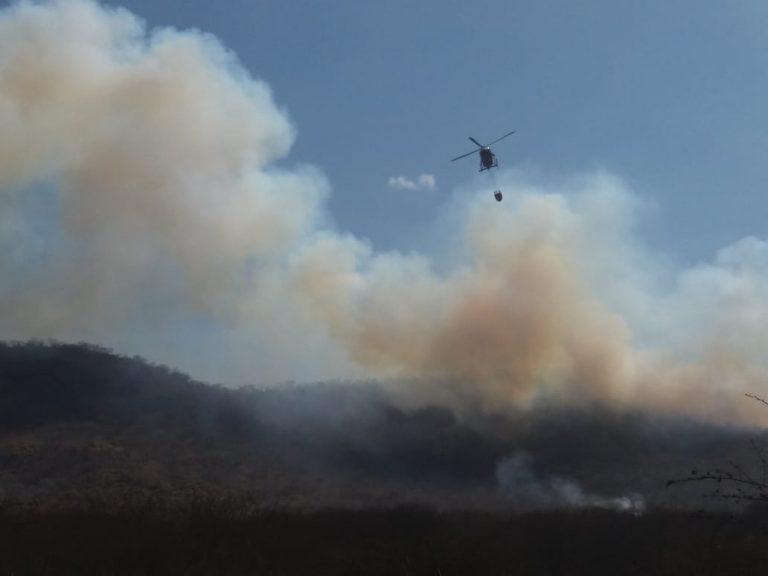 Helicóptero despeja água em foco de incêndio na vegetação nativa