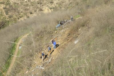 Investigadores percorrem o local do acidente com um helicóptero S-76, que matou nove pessoas, incluido o jogador de basquetebol Kobe Bryant, em 26 de janeiro de 2020.