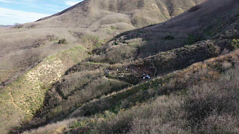 Uma imagem estática de um vídeo de drone duplicando a trajetória de voo do helicóptero de acidente. A imagem captura a posição e a altitude do último alvo do ADS-B do helicóptero. Imagem NTSB