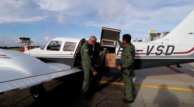 Equipe do GTA retirando caixa com testes de avião — Foto: SSP/SE