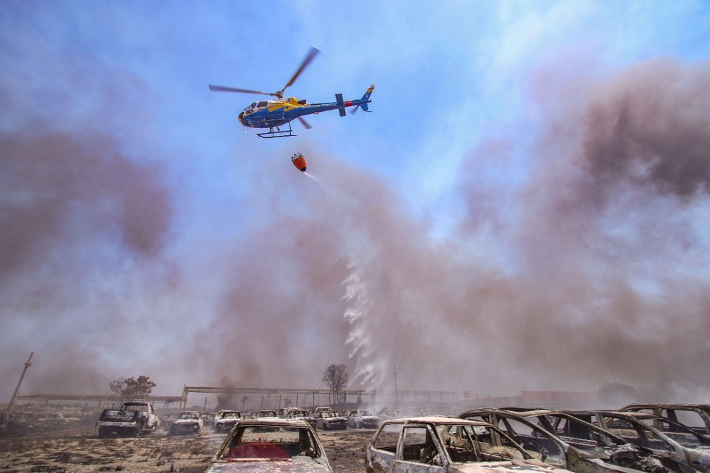 Helicóptero do Centro Integrado de Operações Aéreas (Ciopaer) lançando água sobre os veículos — Foto: Luiz Henrique Machado/Governo do Tocantins